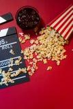 Концепция кино Clapperboard, билет и попкорн на красном backgrou Стоковая Фотография