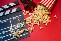 Концепция кино Clapperboard, билет и попкорн на красном backgrou стоковые фотографии rf