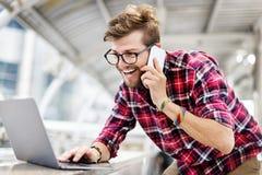 Концепция компьтер-книжки просматривать Smartphone молодого человека говоря Стоковые Фото