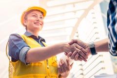 Концепция конструкции и инженера Рабочий-строитель в защитной форме тряся руки встречая для архитектурноакустического проекта стоковые фото