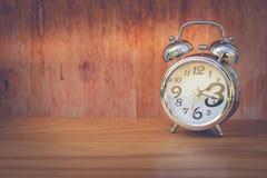 Концепция контроля времени: Будильник положенный на деревянный стол в винтажный стиль стоковое фото rf