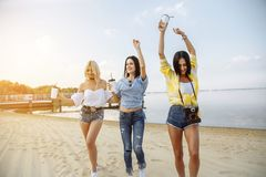 Концепция летних каникулов, праздников, перемещения и людей - группа в составе усмехаясь молодые женщины танцуя на пляже Стоковые Изображения RF