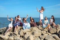 Концепция летних каникулов, праздников, перемещения и людей - группа в составе усмехаясь молодые женщины на пляже Стоковые Фотографии RF