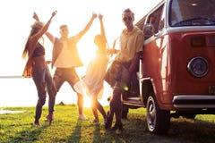 Концепция летних отпусков, поездки, каникул, перемещения и людей - усмехаясь молодые друзья hippie имея потеху над минифургоном стоковые фото