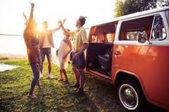 Концепция летних отпусков, поездки, каникул, перемещения и людей - усмехаясь молодые друзья hippie имея потеху над минифургоном стоковые изображения rf