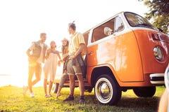 Концепция летних отпусков, поездки, каникул, перемещения и людей - усмехаясь молодые друзья hippie имея потеху над минифургоном стоковая фотография