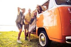 Концепция летних отпусков, поездки, каникул, перемещения и людей - усмехаясь молодые друзья hippie имея потеху над минифургоном стоковое фото