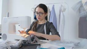 Концепция мелкого бизнеса и хобби Дизайнерская одежда молодой женщины работая на швейной машине в ее студии сток-видео