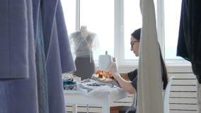 Концепция мелкого бизнеса и хобби Дизайнерская одежда молодой женщины работая на швейной машине в ее студии видеоматериал