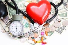Концепция медицинской страховки с красными сердцем, пилюльками и медицинскими инструментами на куче денег Стоковое фото RF