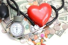 Концепция медицинской страховки с красными сердцем, пилюльками и медицинскими инструментами на куче денег Стоковые Изображения RF