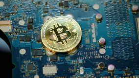 Концепция минирования Bitcoin Ложь монетки бита золота на монтажной плате видеоматериал