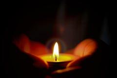 Концепция молитве и надежде свечи освещает в руках Стоковая Фотография