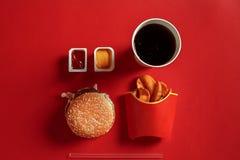 Концепция насмешки вверх по бургеру, картошкам, соусу и питью на красной предпосылке Скопируйте космос для текста и логотипа Стоковые Изображения RF
