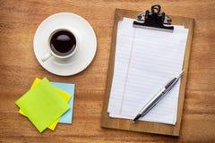 Концепция настольного компьютера - доска сзажимом для бумаги, липкие примечания и кофе Стоковые Изображения RF
