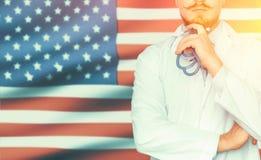 Концепция национальной системы здравоохранения и медицины в Америке США Непознаваемый доктор думает и держит руку около стороны,  стоковое фото