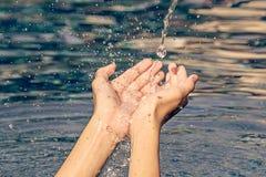 Концепция надежды: человеческая рука с водой падает вниз к ладони Стоковое Фото