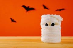 Концепция на хеллоуин Летучие мыши и мумия от опарника, повязк и свечей на оранжевой предпосылке Стоковые Фотографии RF