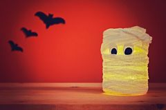 Концепция на хеллоуин Летучие мыши и мумия от опарника, повязк и свечей на оранжевой предпосылке Стоковые Фото
