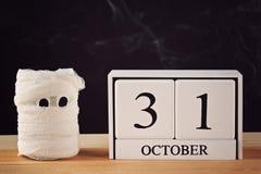 Концепция на хеллоуин Мумия от чонсервной банкы, марли и свечей, деревянного календаря показывая 31-ое октября Стоковые Изображения