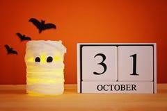 Концепция на хеллоуин Мумия от чонсервной банкы, марли и свечей, деревянного календаря показывая 31-ое октября Стоковые Фотографии RF