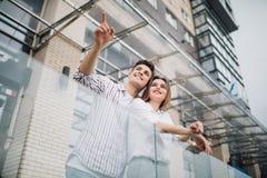 Концепция недвижимости и семьи Молодые пары указали сторона на фронте новой большой современной конструкции дома стоковое фото