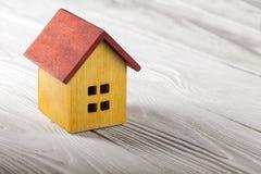 Концепция недвижимости с деревянным домом на белой деревянной предпосылке Концепция имущества идеи по-настоящему, личное свойство стоковое фото