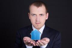 Концепция недвижимости - молодой человек держа небольшой дом в его руках стоковая фотография rf