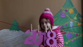 Концепция 2018 Нового Года Красивая малая девушка украшая цифр Нового Года предпосылка покрашенной рождественской елки и сток-видео