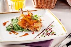 Концепция обедающего в японском ресторане Шпинат гарнирует со сливками и застекленные куриные ножки в пряном соусе стоковая фотография rf