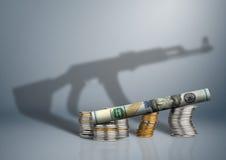 Концепция оборонного бюджета, деньги с тенью оружия стоковые фото