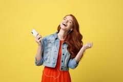 Концепция образа жизни и музыки: Красивая молодая курчавая красная женщина волос в наушниках слушая к музыке и танцуя на ярком Стоковая Фотография RF