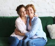Концепция образа жизни, семьи и людей: Счастливая молодая женщина и ее мать дома, счастливая семья стоковое изображение rf