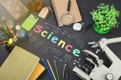 Концепция образования - книги, микроскоп и надпись науки на классн классном стоковая фотография