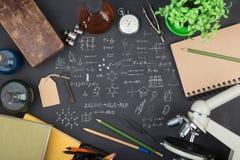 Концепция образования - книги, микроскоп и эскиз науки на классн классном стоковые фотографии rf