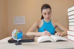 Концепция образования - книги на столе в аудитории делающ девушку ее домашняя работа Стоковые Изображения RF