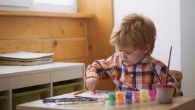 Концепция образования раннего детства, картины, таланта, счастливой семьи и воспитания Милый, серьезный и сфокусированный мальчик сток-видео