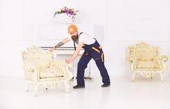Концепция обслуживания поставки Курьер поставляет мебель в случае двигает вне, перестановка Затяжелитель носит кресло 308 латунны стоковая фотография rf