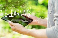 Концепция обучения по Интернету с человеком держа его планшет стоковое изображение