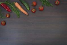 Концепция овощей на деревянной коричневой предпосылке Зеленые огурец и томаты на деревянном столе Морковь и паприка с зелеными цв Стоковые Изображения RF
