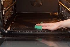 Концепция домашнего хозяйства и домоустройства Scrubbing плита и печь Закройте вверх женской руки при зеленая губка очищая кухню  Стоковое Изображение RF