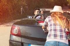Концепция отдыха, поездки, перемещения и людей - счастливые друзья нажимая сломанный автомобиль cabriolet вдоль проселочной дорог Стоковые Изображения