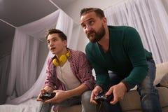 Концепция, отец и сын видеоигры наслаждаясь играющ консоль совместно Стоковые Изображения