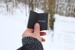 Концепция откройте или Joyrney Рука держа книгу с надписью На предпосылке леса зимы стоковое фото