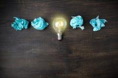 Концепция отличной идеи со скомканным светом - голубая бумага и электрическая лампочка на деревянной предпосылке стоковая фотография rf