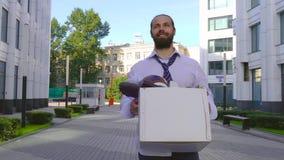 Концепция отставки от работы, рекрутства Работник идет между офисными зданиями с картонной коробкой и видеоматериал
