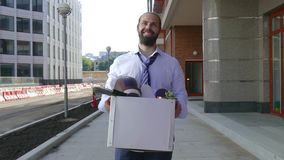 Концепция отставки от работы, рекрутства Работник идет между офисными зданиями с картонной коробкой и сток-видео