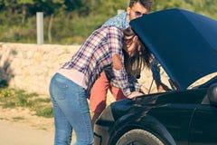 Концепция отдыха, поездки, перемещения и людей - счастливые друзья нажимая сломанный автомобиль cabriolet вдоль проселочной дорог Стоковое Изображение