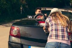 Концепция отдыха, поездки, перемещения и людей - счастливые друзья нажимая сломанный автомобиль cabriolet вдоль проселочной дорог Стоковая Фотография RF