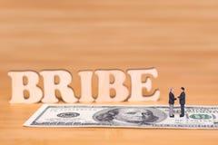 Концепция о коррупции Миниатюрные люди и деньги стоковая фотография rf